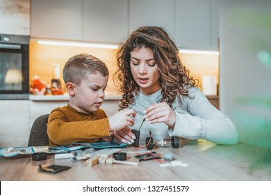 Mom and son concentrate while building a robot. Mother helping son with electronic project. Homeschooling mom teaches son about robotics