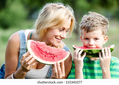 Mom and son are eating watermelon