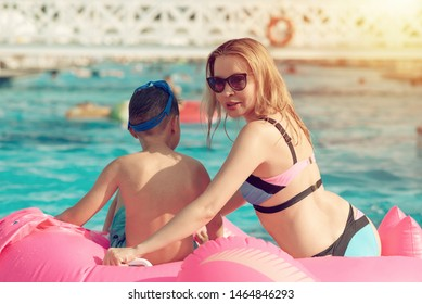 Mom and son enjoy summer holidays. They having fun with pink inflatable floater in resort pool.