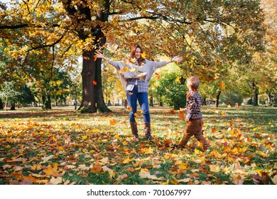 Mom and son having fun with autumn leaves in the park