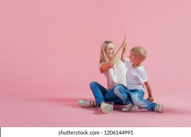 Mom and son high-fiving each other. Beautiful blonde with her baby on a skateboard, pink background