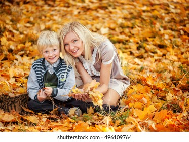 Mom and son holding autumn leaves and smiling