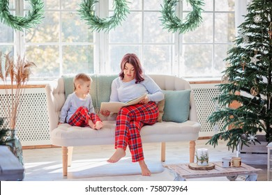 Mom and son in identical pajamas read a book sitting on a sofa in a room with a Christmas decor