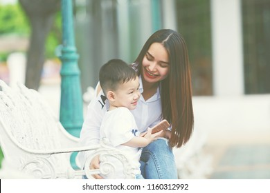 Mom and son laughing between sit at a white chair at park,It's a happy moment.