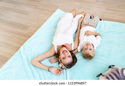 Mom and son lie on the bed and laugh. Happy childhood with fun and entertainment. Family values to spend time together, appreciate loved ones, take care of children, love parents. Beauty faces people
