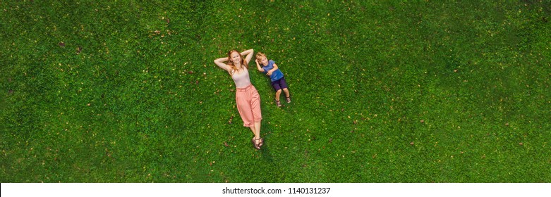 Mom and son are lying on the grass in the park, photos from the drone, quadracopter. BANNER long format