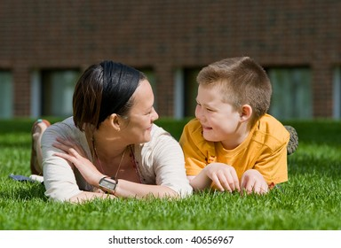 Mom and the son lying on a grass,- they are smiling and talking