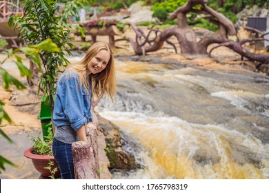 Mom and son on the background of Majestic landscape of waterfall in summer at Dalat, Vietnam