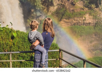 Mom and son on the background of Majestic landscape of Elephant waterfall in summer at Lam Dong Province, Dalat, Vietnam. Look at the rainbow.