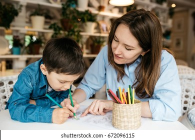 Mom and son painted with colored pencils in a cozy room. She shows him how to color it correctly. Shelves with flower pots on the backgrounds
