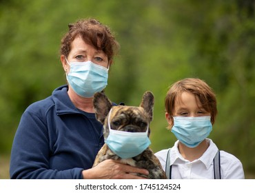 Mom, son and pet French Bull Dog wearing face masks for COVID-19.