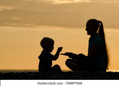 Mom and son are playing on the beach. Silhouettes at sunset
