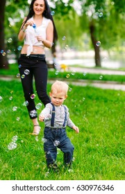 Mom and son are playing with soap bubbles.