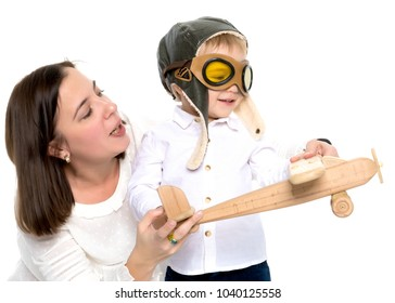 Mom and son are playing with a toy wooden plane. The concept of a happy childhood, raising a child in the family. Isolated on white background.