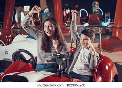 Mom and son rejoice that they won the game on a toy car. Son and mom have fun in the entertainment center together.