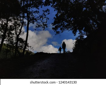 Mom and son silhouette at the top of the hill against blue cloudy sky.