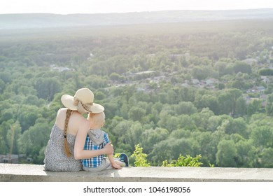 Mom and son sitting on background of green forest and the village away. Back view