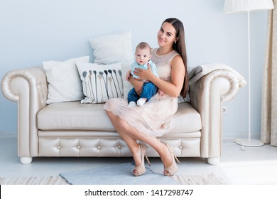 Mom and son are sitting together in the living room on the couch