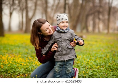 Mom and son with a small child are walking in a spring forest or park, mother's day