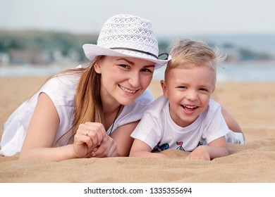 Mom and son smiling lie on sand of beach. Happy little boy son and mother summer. Portrait close-up young woman in hat together with cute blond kid having rest on outdoor, vacation.
