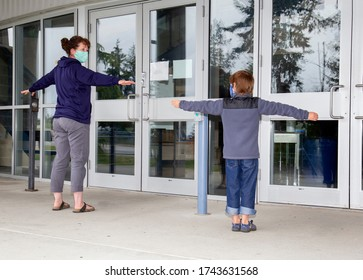 Mom and son standing in front of glass doors with arms outstretched showing the two meter physical distancing while wearing masks.