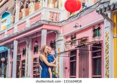 Mom and son are tourists on the Street in the Portugese style Romani in Phuket Town. Also called Chinatown or the old town