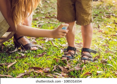 Mom and son use mosquito spray.Spraying insect repellent on skin outdoor.