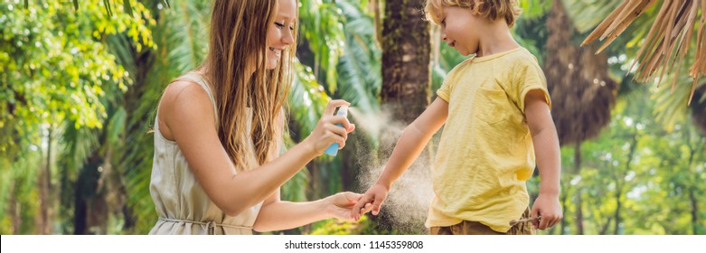Mom and son use mosquito spray.Spraying insect repellent on skin outdoor BANNER, long format