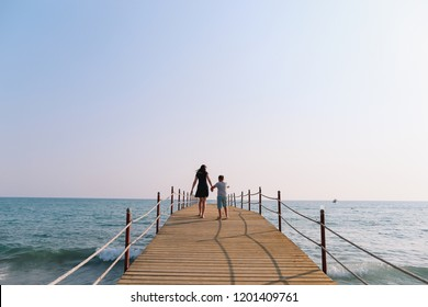 Mom and son walking along the pier. Sea horizon and blue sky. Family vacation at sea. Summer time sea vacation background