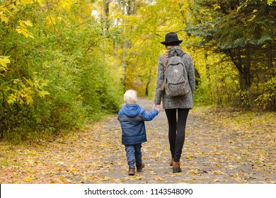 Mom and son are walking in the autumn forest. Back view