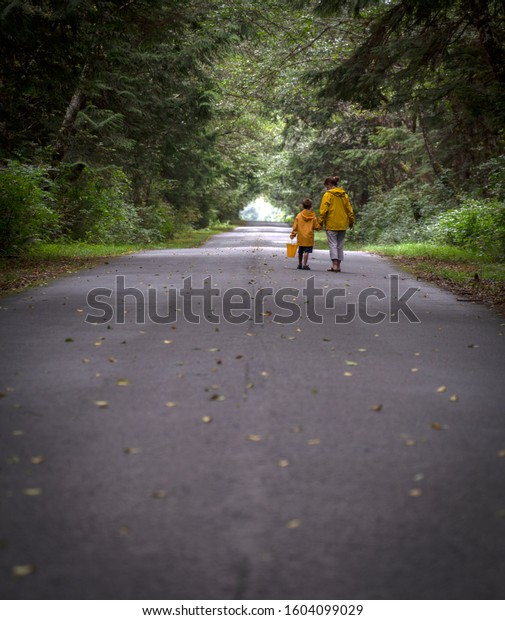 Mom and son walking down a road in the fall wearing yellow rain jackets.