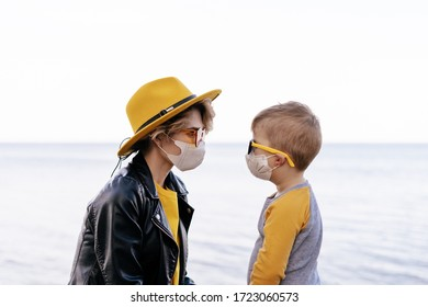 Mom, Son Wearing Face Mask Outside River or Lake. Caucasian Young Woman in Hat and Sunglasses Spend Time Outdoor with Kid. Mother and Boy Looking at each other. Coronavirus Outbreak Quarantine