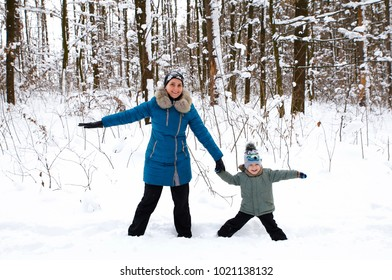 Mom and son in the winter forest playing in the snow Photo for micro-stock