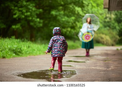 Mom stands behind with umbrellas while her daughter plays in pools after rain