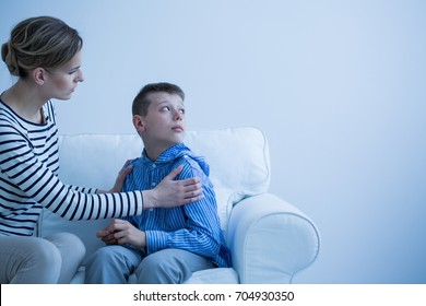 Mom in striped shirt calms her son who has panic attack while sitting on white sofa