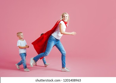 Mom is a superhero. Fun family, a young blond woman in a red Cape and her son, Sons follow mom pink background