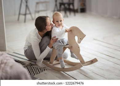Mom supports baby son swinging on a rocking toy horse. Real light interior, caring motherhood concept