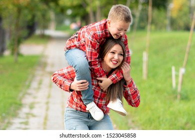 Mom, with a surprised expression on her face, bent over, holds a smiling son on her shoulders.