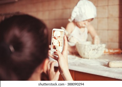 Mom takes photos with her phone like a little boy playing with a fry test on the table in an apron and chef's hat