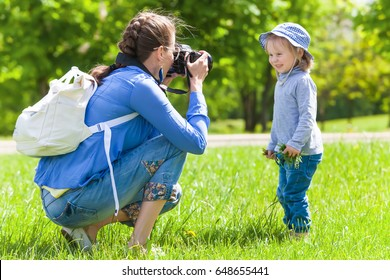 Mom takes pictures of a child in the park in summer