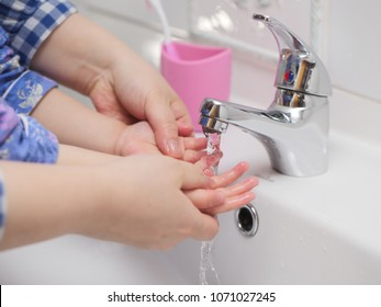 Mom teach baby girl how to washing hand