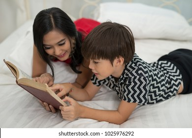 Mom teach son reading a book is on the bed at home. Education Concepts