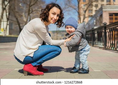 Mom teaches baby to walk on the street. Mom supports her son with her hands, teaches him to stand. A little boy learns to walk.