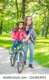 mom teaches her daughter to ride a bicycle in the park