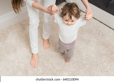 Mom teaches her daughter to walk. Helps and supports the child learning to walk. The child enjoys the first steps.