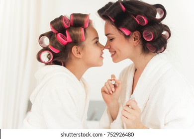 Mom teaches a little daughter to do makeup. They sit in their white bathrobes on the bed in their bedroom. On their heads they have curlers.