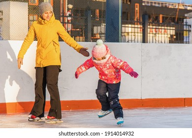 Mom teaches little daughter to skate, winter evening at sunset