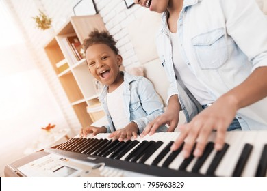 Mom teaches a little girl to play the piano. They play and sing songs. They are having fun.
