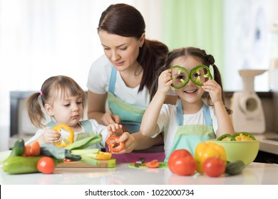 Mom teaches two kids daughters to cook at the kitchen table with raw food