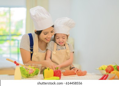 mom teaching cute girl cooking healthy salad for the first time. first lesson and healthy lifestyle concept.